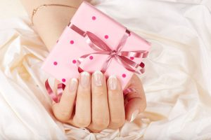 pink gift box with ribbon in lady's hand