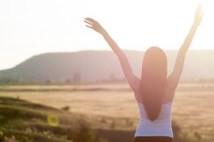woman happy with life strtching to the sunrise