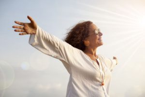 Woman standing arms stretched feeling happy